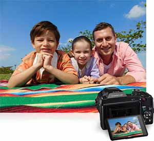 Photo of a dad and kids on a blanket with the camera inset with the same photo on the LCD