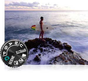Nikon COOLPIX P900 photo of a surfer on jetties and mode dial showing full manual control