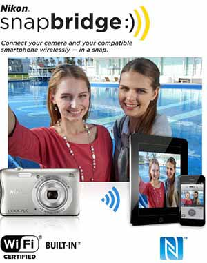 Nikon COOLPIX S3700 photo of a two girls taking a selfie, using the S3700, along with the snapbridge logo and tablet and smart phone