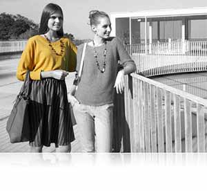Nikon COOLPIX S3700 black and white photo of two women near a railing outdoors, with one woman's shirt in yellow