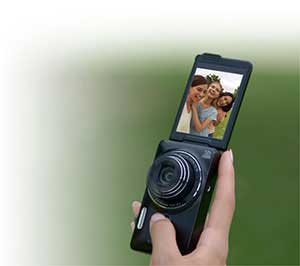 Photo of the COOLPIX S6900 in a person's hand, with the LCD swiveled to show a photo