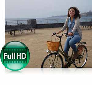 Nikon COOLPIX S7000 photo of a woman on a bike on a pier, and the Full HD video icon inset