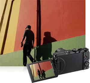 Nikon COOLPIX S9900 photo of a man against a colorful wall highlighting the Vari-angle LCD