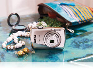 Photo of the COOLPIX S01 with purse and jewelry showing small size