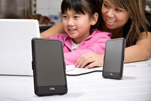 This is a little girl and mother using a computer with the speakers