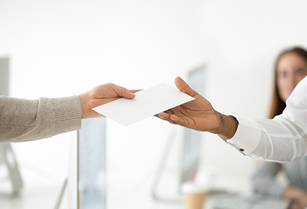 Image of two hands passing an envelope between them