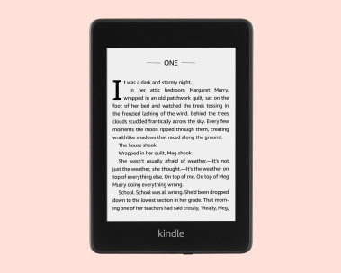 A Kindle with the screen turned on rests atop a pink background