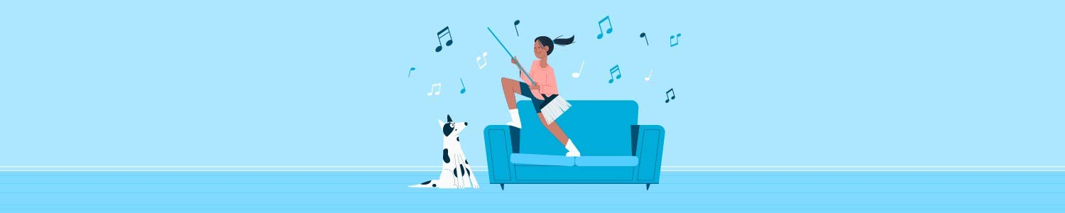 A woman rocking out on the couch using a broom as an air guitar.
