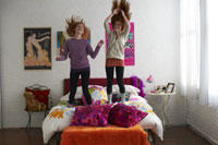 two girls jumping on a bed