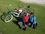 Couple posing on grass with their bikes