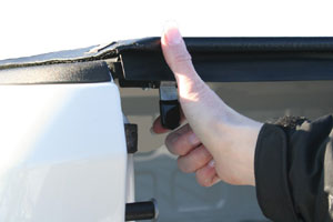 The trigger latch of a TruXedo Lo Profile QT soft roll-up tonneau cover operated with a single finger