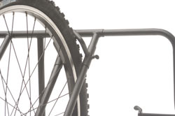 Close-up of a mountain bike tire held in place by adjustable spacers built into the Heininger Advantage BedRack Truck 4 Bike Carrier