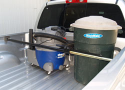 The Heininger HitchMate Cargo Stabilizer Bar securing a shop vac and an upright trash can in the back of a pickup