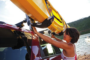 A woman loading a kayak to her roof rack using the Thule 897XT Hullavator Kayak Roof Rack Mount Carrier