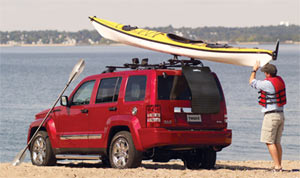 Paddler loading a kayak while using a Thule 854 Water Slide Kayak Carrier Accessory Mat