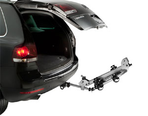 Thule Helium 2-Bike Hitch Carrier with carrier arm angled down and hatchback up