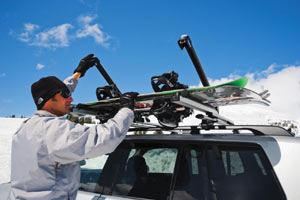 A snowboarder unloading a Thule 91726 Universal Pull Top Ski and Snowboard Carrier