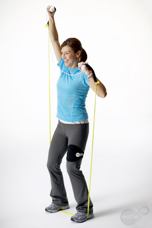 Woman doing a side stretch with Wii Remote/nunchuck and resistance band in EA Sports Active: More Workouts