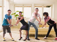 Four people dancing using Wii Remotes in Just Dance