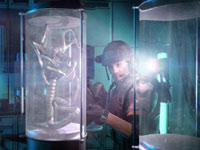 A marine examining a confined Facehugger variety of alien up close in Aliens: Colonial Marines