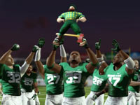 The Spartans of Michigan State celebrating a victory over the rival Wolverines with the traditional hoisting of the Paul Bunyan Trophy, in NCAA Football 13