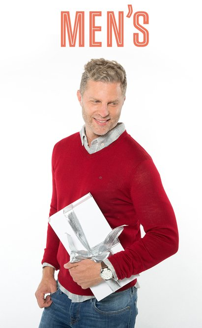 Mens. Image of a man in a red sweater holding a present.