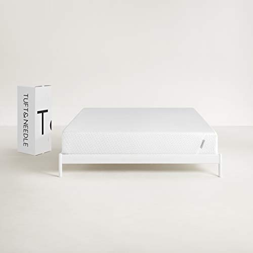 Tuft & Needle Toddler Mattress on all-white wooden bed with white and black packaging box beside it