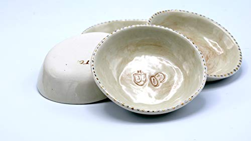 A set of 4 small Hanukkah bowls featuring dreidels and gelt, accented with yellow and white gold along the rim by Goldberg Judaica
