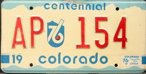 (Colorado Centennial License Plate red numbers on white )