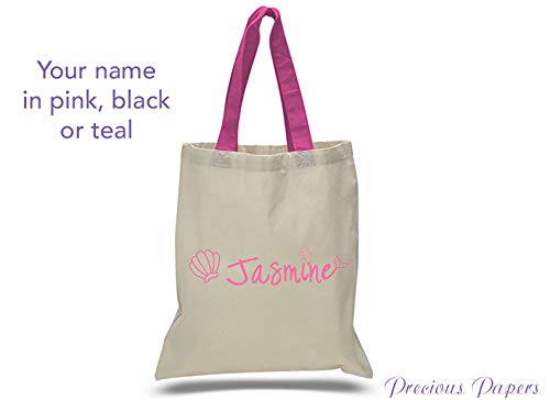 Personalized mermaid design on a natural canvas tote bag with pink handles for a cruise or beach trip vacation pool bag tote in choice of color for the name]()