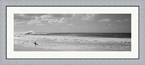 Surfer standing on the beach in black and white, Oahu, Hawaii by Panoramic Images Framed Art Print Wall Picture, Flat Silver Frame, 45 x 20 inches by Great Art Now