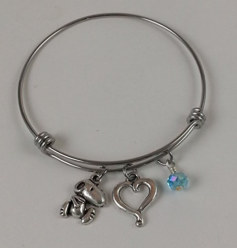 Snoopy Stainless Steel Adjustable Bangle Charm Bracelet with Open Heart and Light Blue Dangle.]()
