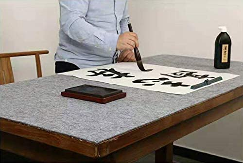 Grey felt mat on a table where someone is using ink and a brush to write calligraphy