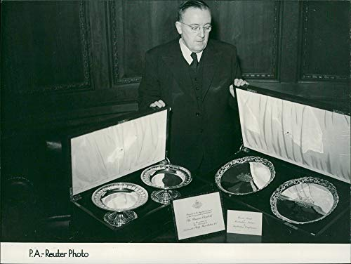 Vintage photo of elizabeth princess and tow hand engraved and chased silver dessert dishes embossed with a 24 carat gold commonwealth.