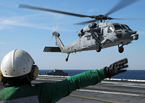 A Sailor assigned to Helicopter Sea Combat Squadron (HSC) 9 signals to an MH-60S Sea Hawk helicopte