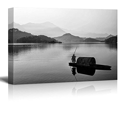 Black and White Canoe with a Man Rowing Down a Lake Towards The Mountains