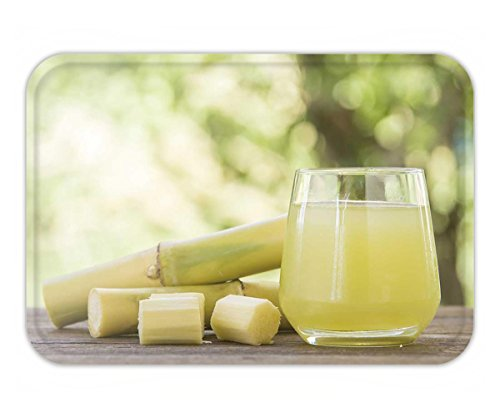 Beshowere Doormat fresh squeezed sugar cane juice in glass with cut pieces cane on nature background