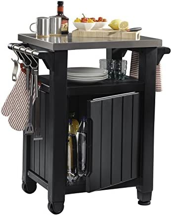 417bWE%2BmeHL. AC Keter Unity Portable Outdoor Table and Storage Cabinet with Hooks for Grill Accessories-Stainless Steel Top for Patio Kitchen Island or Bar Cart, Dark Grey    This plastic outdoor kitchen storage table with wheels combines two storage solutions in one, providing a stainless steel top for serving drinks or condiments and a cupboard for storing extra supplies. It works perfectly for a family barbecue or any friendly gatherings on the deck, giving you extra serving and storage space for plates, water bottles and more. Place snacks on the durable surface for friends to grab any time, and keep cloth napkins or grilling utensils hung easily within reach on the additional hooks.