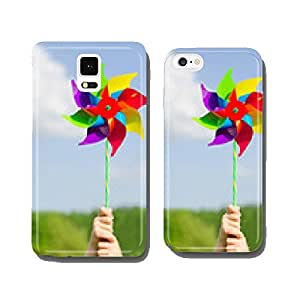 Child hands holding pinwheel against blue sky. cell phone cover case iPhone6