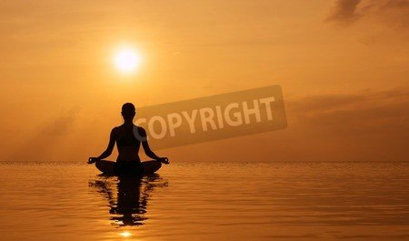 Silueta Young Woman Practicing Yoga on the beach at sunset ...