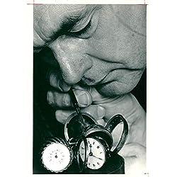 Vintage photo of geoffrey evans adjusts his clock