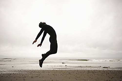 An Individual Wearing A Wet Suit Jumping In Mid-Air On A Beach French Beach British Columbia Canada Poster Print (19 x - Wearing Wetsuit