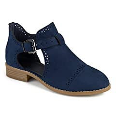 Show off chic style with cut-out booties by Journee Collection. These ankle boots feature faux suede uppers with pin-hole decoration and modern cut-outs at the sides of each foot. Stacked block heels finish the look