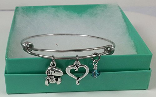 Snoopy Stainless Steel Adjustable Bangle Charm Bracelet with Open Heart and Blue Dangle.]()
