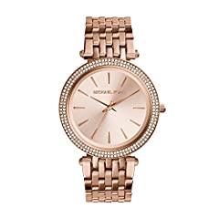 Crystals cover the bezel of this glamorous Michael Kors watch, designed with slim markers on the brushed dial. Hinged-snap clasp.