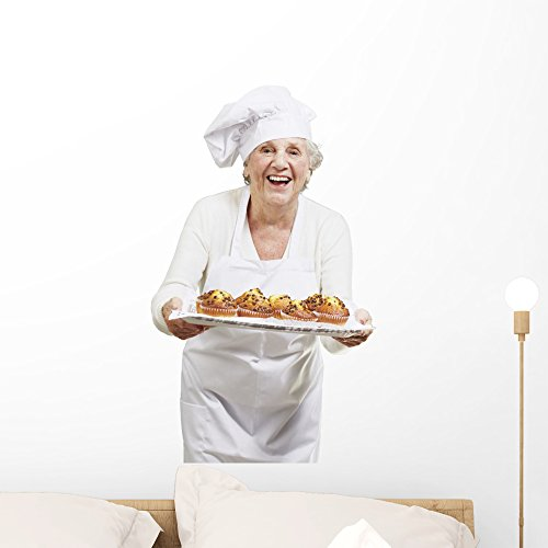 Wallmonkeys WM117856 Senior Woman Cook Holding a Tray with Muffins Against a White Ba Peel and Stick Wall Decals (24 in H x 19 in W), Medium