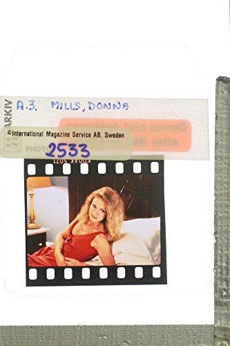 (Slides photo of Donna Mills lying in the bed.)