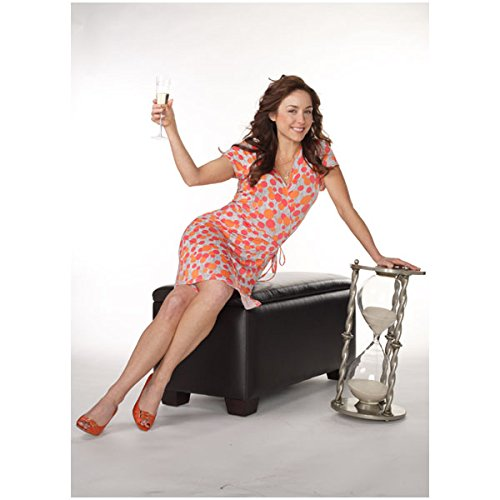 Erin Leather (Being Erica Erin Karpluk as Erica Sitting on Leather Ottoman in Orange and Pink Flowered Dress Holding Champagne Flute 8 x 10 inch photo)