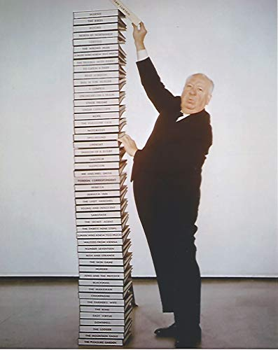 Alfred HItchcock standing next to tall stack of movie notebooks 8 x 10 Movie Photo - 004 ()