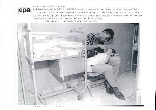 - Vintage photo of Haiti port au prince:a haithian father feed his young son.